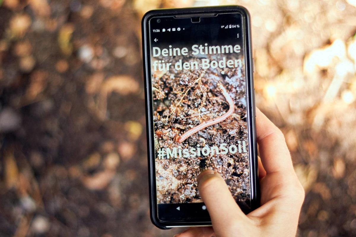"""Smartphone in der Hand mit Foto: """"Deine Stimme für den Boden – an #MissionSoil beteiligen"""" (Foto: Niko Martin)"""